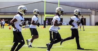 May 25, 2017; New Orleans, LA, USA; New Orleans Saints running back Travaris Cadet (left) and running back Adrian Peterson (left middle) and running back Trey Edmunds (right middle) and running back Alvin Kamara (right) participate in running drills durin