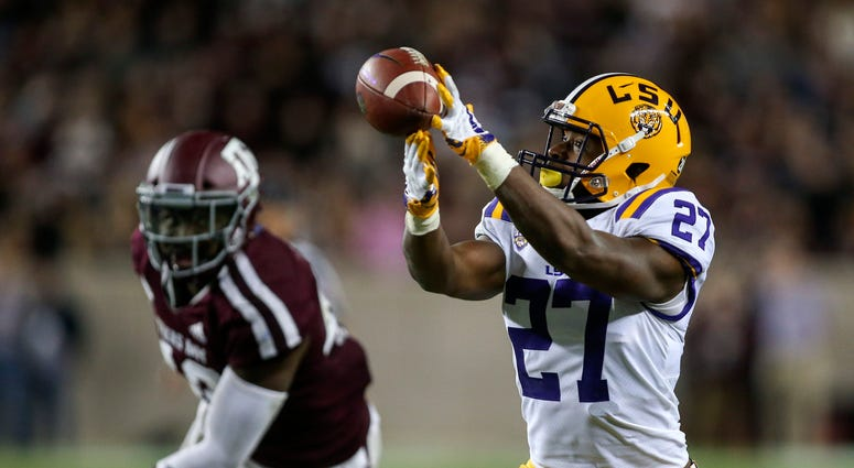 LSU Tigers running back Lanard Fournette (27) is unable to make a reception as Texas A&M Aggies linebacker Otaro Alaka (42) defends during the third quarter at Kyle Field.