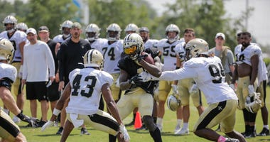ew Orleans Saints running back Alvin Kamara (41) is tackled by defensive end Cameron Jordan (94) and free safety Marcus Williams (43) during training camp practice at the Ochsner Sports Performance Center.