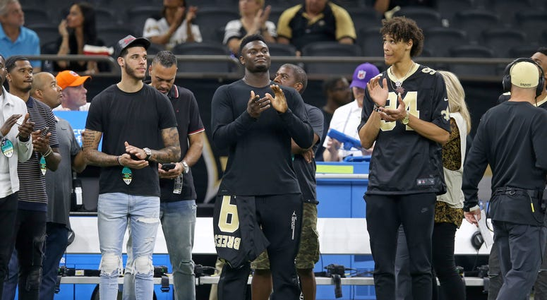 New Orleans Pelicans players Lonzo Ball (left) and Zion Williamson (center) and Jaxson Hayes (right) look on from the sidelines before the game between the New Orleans Saints and the Houston Texans at the Mercedes-Benz Superdome.