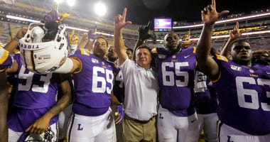 LSU Tigers head coach with offensive lineman Charles Turner (69) and offensive lineman Jakori Savage (65) and offensive lineman Michael Smith (63) after a win against the Northwestern State Demons at Tiger Stadium.