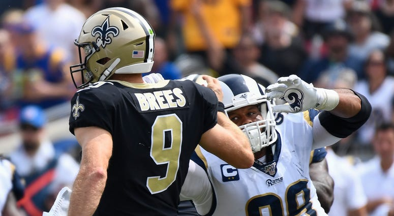 Los Angeles Rams defensive tackle Aaron Donald (99) charges toward New Orleans Saints quarterback Drew Brees (9) after a pass pay in the 1st quarter at Los Angeles Memorial Coliseum. Brees would leave the game with a hand injury after the play.