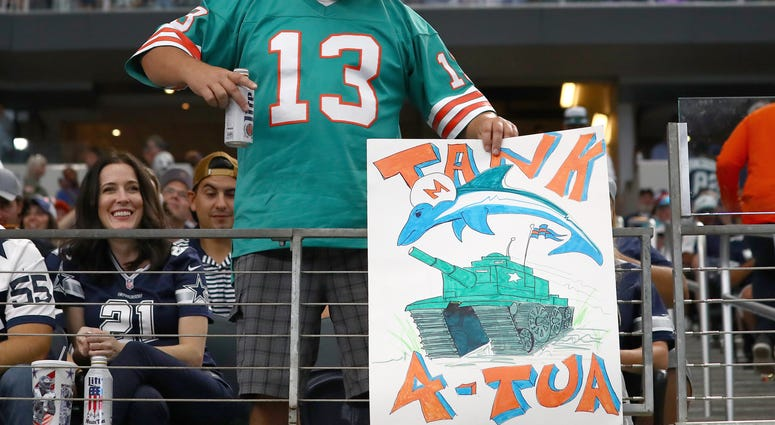 Miami Dolphins fan holds a tanking sign during the game against the Dallas Cowboys at AT&T Stadium.