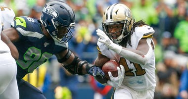 New Orleans Saints running back Alvin Kamara (41) rushes against Seattle Seahawks defensive end Rasheem Green (98) during the fourth quarter at CenturyLink Field.