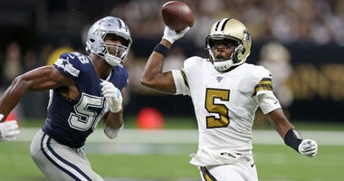 New Orleans Saints quarterback Teddy Bridgewater (5) looks to throw while chased by Dallas Cowboys defensive end Robert Quinn (58) in the second quarter at the Mercedes-Benz Superdome.