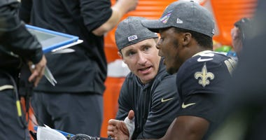 New Orleans Saints quarterback Drew Brees (9) talks to Teddy Bridgewater (5) on the bench in the second half against the Tampa Bay Buccaneers at the Mercedes-Benz Superdome.
