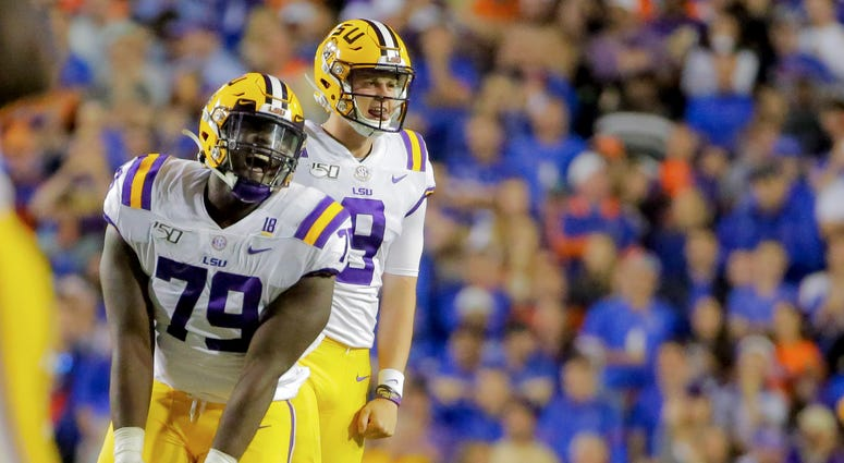 LSU Tigers quarterback Joe Burrow (9) and center Lloyd Cushenberry III (79) celebrate after a touchdown against the Florida Gators during the fourth quarter at Tiger Stadium.