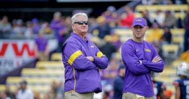 LSU Tigers offensive coordinator Steve Ensminger and passing game coordinator Joe Brady (right) watch during warm ups prior to kickoff against the Auburn Tigers at Tiger Stadium.
