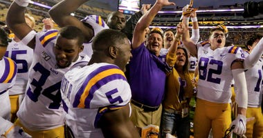 LSU Tigers head coach Ed Orgeron celebrates with players after defeating the Auburn Tigers 23-20 at Tiger Stadium.