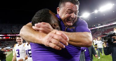 LSU Tigers head coach Ed Orgeron celebrates with a coach after defeating the Alabama Crimson Tide 46-41 during the second half of an NCAA college football game at Bryant-Denny Stadium.