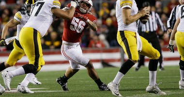 Badgers linebacker Zach Baun tries to get past Iowa offensive tackle Alaric Jackson on his way to quarterback Nate Stanley.
