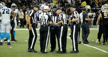 Officials huddle during Saints/Panthers game