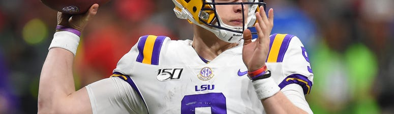 LSU Tigers quarterback Joe Burrow (9) rolls out to pass against the Georgia Bulldogs during the third quarter of the the 2019 SEC Championship Game at Mercedes-Benz Stadium.