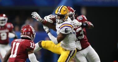 LSU Tigers wide receiver Terrace Marshall Jr. (6) catches a pass against Oklahoma Sooners cornerback Parnell Motley (11) and linebacker DaShaun White (23) during the third quarter of the 2019 Peach Bowl college football playoff semifinal game.