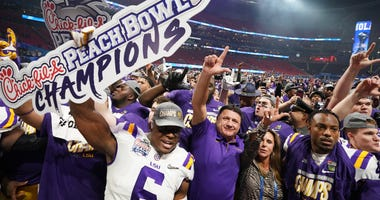 LSU Tigers head coach Ed Orgeron celebrates with his players and his wife Kelly after defeating the Oklahoma Sooners in the 2019 Peach Bowl college football playoff semifinal game at Mercedes-Benz Stadium.