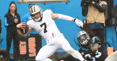 New Orleans Saints quarterback Taysom Hill (7) scores a touchdown as Carolina Panthers free safety Tre Boston (33) defends in the third quarter at Bank of America Stadium.