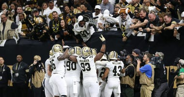 The New Orleans Saints defense celebrates with fans after a fumble recovery against the Minnesota Vikings during the first quarter of a NFC Wild Card playoff football game at the Mercedes-Benz Superdome.