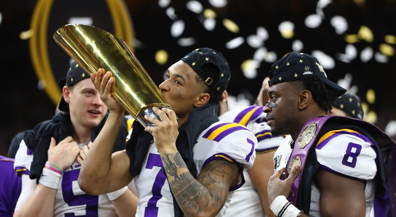 LSU Tigers safety Grant Delpit (7) kisses the national championship trophy after defeating the Clemson Tigers in the College Football Playoff national championship game at Mercedes-Benz Superdome.