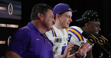 ; From left LSU Tigers head coach Ed Orgeron, quarterback Joe Burrow (9) and linebacker Patrick Queen (8) at a press conference after the College Football Playoff national championship game against the Clemson Tigers at Mercedes-Benz Superdome.