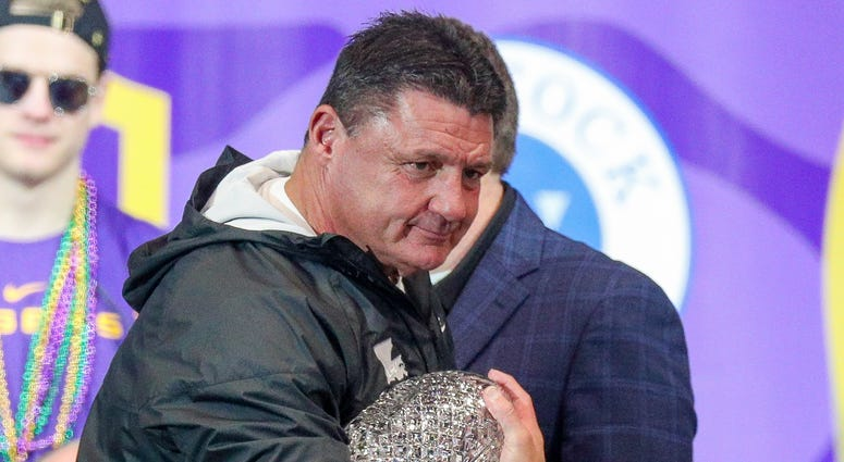 LSU Tigers head coach Ed Orgeron holds the AFCA Coaches' Trophy presented by Amway during the LSU championship trophy presentation at Pete Maravich Assembly Center. Stephen Lew-USA TODAY Sports