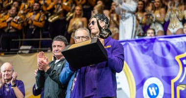 LSU Tigers quarterback Joe Burrow hoists the Heisman Trophy during the LSU Tigers College Football Playoff national championship celebration and parade.