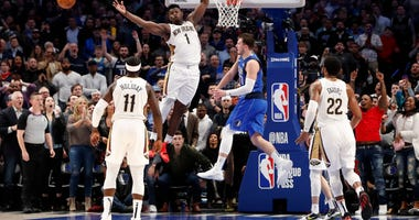 Dallas Mavericks guard Luka Doncic (77) passes past New Orleans Pelicans forward Zion Williamson (1) in overtime at American Airlines Center.