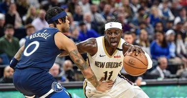 New Orleans Pelicans guard Jrue Holiday (11) controls the ball as Minnesota Timberwolves guard D'Angelo Russell (0) defends during the second quarter at Target Center.