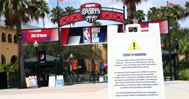 An overview of ESPN Wide World of Sports Complex with a COVD-19 warning sign where the NBA season restart and playoffs with be played.