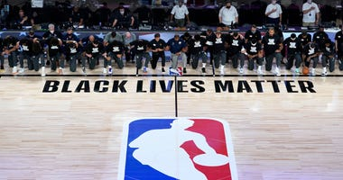 Members of the New Orleans Pelicans and Utah Jazz kneel together around the Black Lives Matter logo on the court during the national anthem before the start of an NBA basketball game.