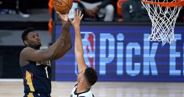 New Orleans Pelicans player Zion Williamson, left, shoots over Utah Jazz player Georges Niang during the first half of an NBA basketball game.