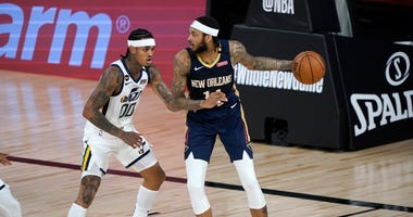 New Orleans Pelicans' Brandon Ingram, right, looks to pass around Utah Jazz's Jordan Clarkson (00) during the first half of an NBA basketball game.