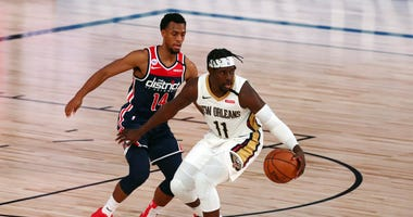 New Orleans Pelicans guard Jrue Holiday (11) handles the ball against Washington Wizards guard Ish Smith (14) during the fourth quarter in an NBA basketball game at Visa Athletic Center.