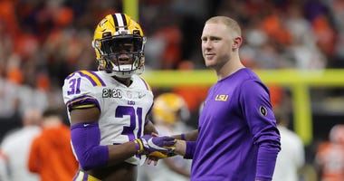 LSU Tigers safety Cameron Lewis (31) talks with passing game coordinator Joe Brady before the College Football Playoff national championship game against the Clemson Tigers at Mercedes-Benz Superdome.