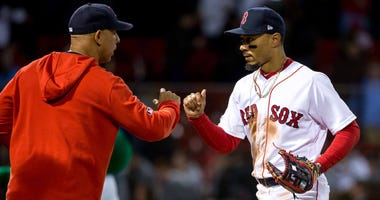 Boston Red Sox manager Alex Cora bumps fists with Mookie Betts after a game on April 25, 2019.