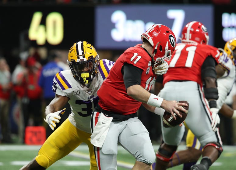 LSU Tigers linebacker Damone Clark (35) tackles Georgia Bulldogs quarterback Jake Fromm (11) in the first quarter in the 2019 SEC Championship Game at Mercedes-Benz Stadium.