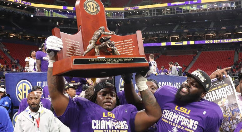 LSU Tigers celebrate with the 2019 SEC Championship trophy after their win against the Georgia Bulldogs in the 2019 SEC Championship Game at Mercedes-Benz Stadium.