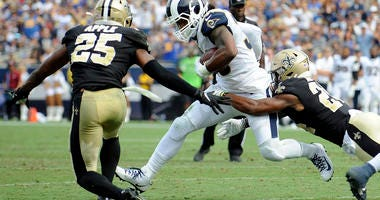 Los Angeles Rams running back Todd Gurley (30) runs the ball against New Orleans Saints cornerback Eli Apple (25) during the second half at Los Angeles Memorial Coliseum.