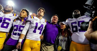 LSU Tigers head coach Ed Orgeron celebrates with his players after defeating the Texas A&M Aggies at Tiger Stadium.