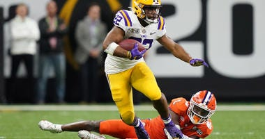 LSU Tigers running back Clyde Edwards-Helaire (22) runs past Clemson Tigers cornerback Derion Kendrick (1) in the fourth quarter in the College Football Playoff national championship game at Mercedes-Benz Superdome.