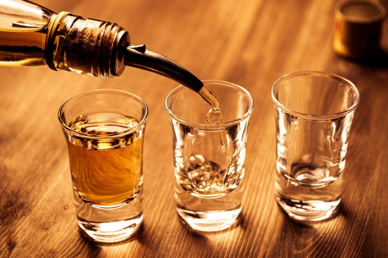 Shots of alcohol are being poured into shot glasses.