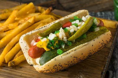 A Chicago style hot dog with mustard, relish, onion, tomato, pickle, sport peppers, and celery salt.