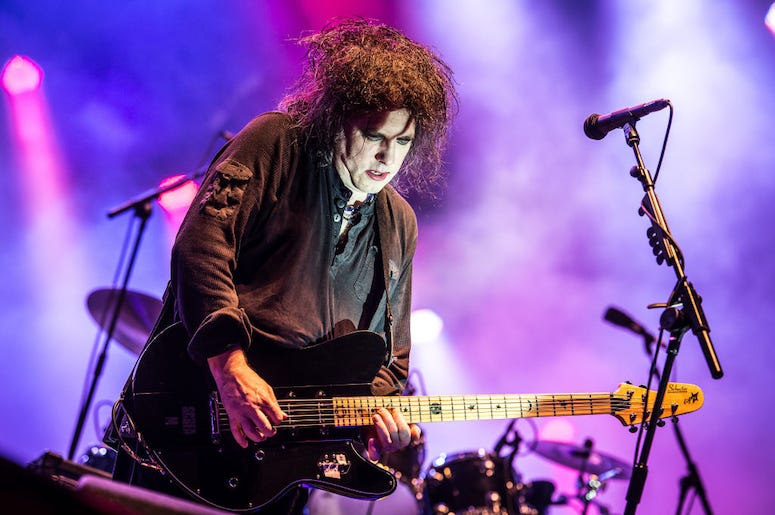 Robert Smith of The Cure plays guitar during a concert.
