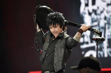 Bille Joe Armstrong of Green Day plays guitar behind his head.