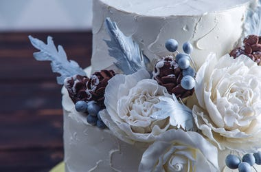 Delicate white bunk wedding cake decorated with an original design using mastic roses
