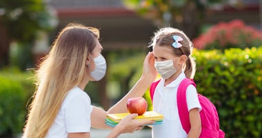 Woman drops off child at school while both wear masks