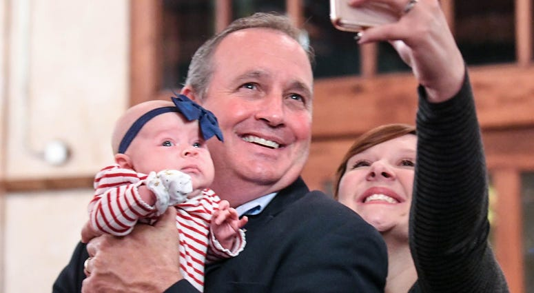 U.S. Rep. Jeff Duncan, middle, holds Ellyson Duncan, the baby of his niece in law Somer Duncan, right, getting a selfie photo, minutes before he was projected to win his fifth term in District 3, during election night party in Anderson on Tuesday, Novembe