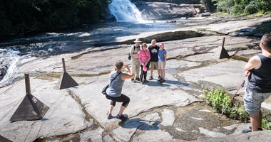 Visitors to Triple Falls in DuPont State Recreational Forest, view the falls from the roped-in viewing area at the base of the falls Thursday, July 26, 2018. 636685587642086186-DuPontFalls-MB2-07262018.jpg