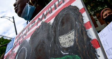 """5/31/20; Greenville, SC, USA: Shamira Scott holds a painting \""""Black Lives Matter\"""" her friend painted for her, during a protest remembering George Floyd at Falls Park in Greenville 5/31/20. Ken Ruinard-Staff via USA TODAY NETWORK"""
