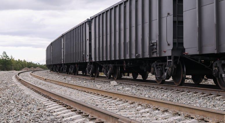 Gray Rail Cars Travel Down Train Tracks - Getty Images