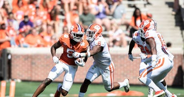 Clemson wide receiver Tee Higgins (5) attempts to break through a tackle by Clemson linebacker Mike Jones Jr. (6) during the Spring Game at Memorial Stadium Saturday, April 6, 2019.